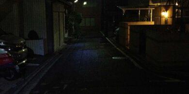 暗く細い通りで探偵が浮気調査の張り込み中
